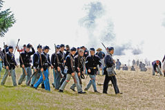 Civil War reenactors marching across a battlefield. Royalty Free Stock Images