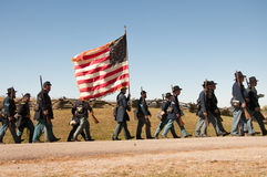 Civil War Union soldiers march with flag. Royalty Free Stock Photo