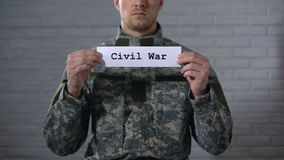 Civil war word written on sign in hands of male soldier, cruelty and death. Stock footage stock video footage