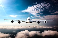 Civil wide-body plane in flight. Aircraft flying on a high altitude above the clouds. Airplane front view Stock Images