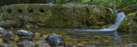 Civilization and nature. Water pipe and mountain river Stock Images