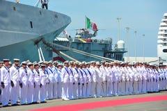 Civitavecchia Roma Itália alguns marinheiros da marinha italiana distribuída sob o navio de guerra alpino que espera as autoridad Fotos de Stock