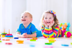 Cjildren playing with wooden toys. Kids playing with wooden toys. Two children, cute toddler girl and funny baby boy, playing with wooden toy blocks, building stock image