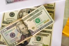 Ckose av oss 20 amerikanska dollarpengarräkningar fördelade upp aroundo över en vit bakgrund Arkivfoton