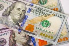 Ckose av oss 100 amerikanska dollarpengarräkningar fördelade upp aroundo över en vit bakgrund Royaltyfria Bilder