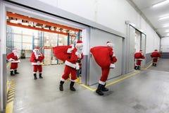 Cláusulas de Santa que deixam um centro de distribuição do presente Foto de Stock