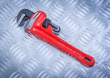 Clé à tube sur le concept creusé des rigoles de construction de fond en métal Image stock
