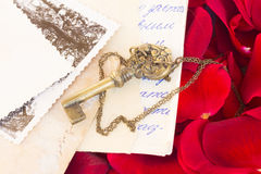 Clé avec les pétales de rose et le vieux courrier Photo libre de droits