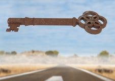 clé 3D rustique flottant au-dessus de la route de désert Images stock