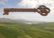 clé 3D rustique flottant au-dessus du paysage vert Photo stock