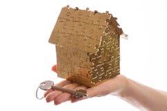 clé de maison et de maison sur une main femelle Photo stock