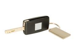 Clé de véhicule avec le keychain et la plaque signalétique d'isolement sur le blanc Photographie stock libre de droits