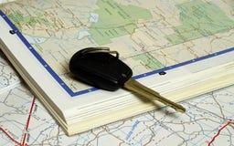 Clé de véhicule sur deux livres ouverts de carte Images libres de droits