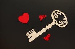 Clé de vintage avec les coeurs rouges sur le fond noir Image stock