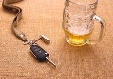 Clé de voiture avec l'accident et la tasse de bière Images stock