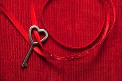 Clé en forme de coeur et ruban rouge sur le velours Images libres de droits