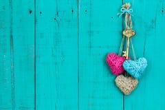 Clé et coeurs accrochant sur la porte en bois photographie stock libre de droits