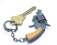 Clé sur une clé-chaîne d'arme à feu Images stock