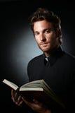 Clérigo joven que sostiene la biblia santa Fotografía de archivo libre de regalías