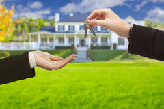 Clés de Handing Over House d'agent devant la nouvelle maison images stock