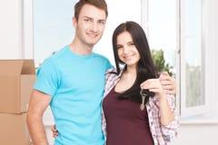 Clés de leur nouvelle maison Jeunes couples gais tenant la clé Images stock