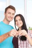Clés de leur nouvelle maison Jeunes couples gais tenant la clé Photographie stock