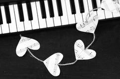Clés de piano et coeurs de la musique sur un fond noir Image libre de droits