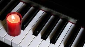 Clés de piano et lumière de bougie banque de vidéos