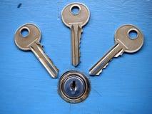 Clés et un trou de la serrure sur une porte bleue Photographie stock libre de droits