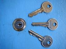 Clés et un trou de la serrure sur une porte bleue Image stock