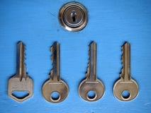 Clés et un trou de la serrure sur une porte bleue Photo stock