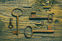 Clés médiévales rouillées sur portée la table en bois Photographie stock libre de droits