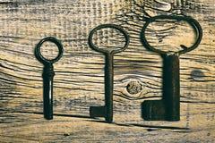 Clés médiévales rouillées sur portée la table en bois Image libre de droits
