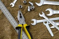 Clés, pinces, ligne en métal sur un tissu brun rugueux Photo stock