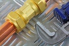 Clés réglables serrant le pièce en t-montage sur la canalisation de cuivre de 15mm sur un fond blanc Photos libres de droits