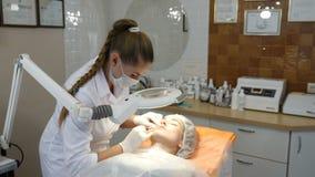 Clínica da beleza Esteticista nas luvas que fazem a injeção do envelhecimento da cara em uma pele fêmea Uma mulher obtém a cosmet vídeos de arquivo