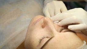 Clínica da beleza Mãos do esteticista nas luvas que fazem a injeção do envelhecimento da cara em uma pele fêmea Uma mulher obtém  video estoque