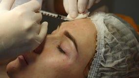 Clínica da beleza Mãos do esteticista nas luvas que fazem a injeção do envelhecimento da cara em uma pele fêmea Uma mulher obtém  filme