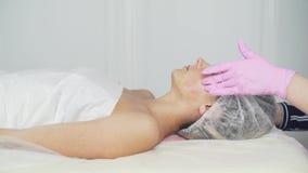 Clínica da beleza Uma mulher obtém a beleza o procedimento facial da cosmetologia video estoque