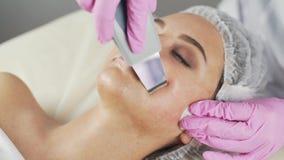 Clínica da beleza Uma mulher obtém a beleza o procedimento facial da cosmetologia vídeos de arquivo