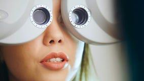 Clínica da oftalmologia - mulher verifica a visão pelo equipamento moderno - exame de olhos, fim acima Imagem de Stock Royalty Free