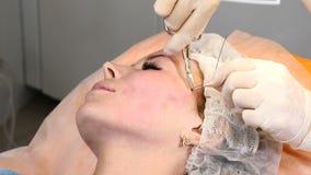 Clínica de Healtcare El cliente femenino joven consigue procedimiento de la elevación de cara del hilo Cosmetólogo en los guantes almacen de metraje de vídeo