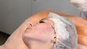 Clínica de la belleza El cliente femenino joven consigue la elevación de cara del hilo Cosmetologist en los guantes que hacen la  almacen de metraje de vídeo