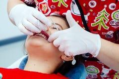 Clínica limpia de la pequeña de la muchacha de los dientes del dentista de los niños de la oficina del tratamiento del doctor del Fotografía de archivo