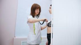 Clínica médica Doutor que trabalha com um estetoscópio que verifica a batida do coração do paciente filme