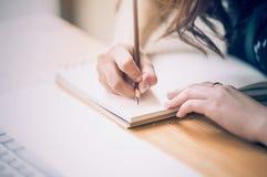 Clôturez des mains femelles de concepteur au dessin de lieu de travail quelque chose Photo stock