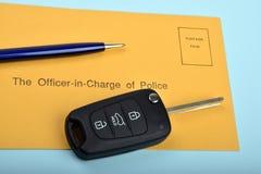 Clé de voiture avec une enveloppe bleue de stylo et de police Photos stock