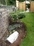 Clôturé le jardin avec le mur en pierre de bloc dans la fin d'été Image stock