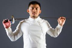 Clôture de l'athlète posant avec une épée ou une épée sur le fond gris Photo stock