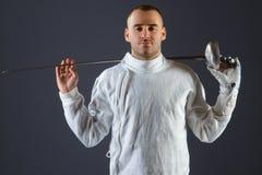 Clôture de l'athlète posant avec une épée ou une épée sur le fond gris Photo libre de droits